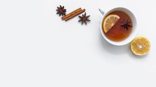 Warmer tee mit zitrone und gewürzen daneben