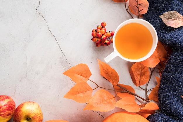 Warmer tee und herbstlaub auf rissiger oberfläche