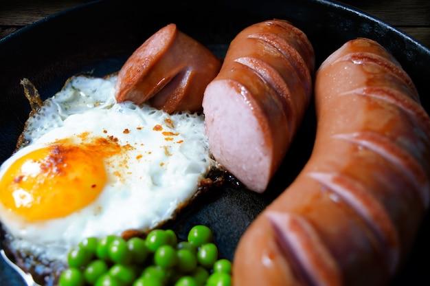 Warmes frühstück in einer pfanne mit bratwürsten und erbsen