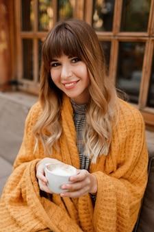 Warmes gemütliches porträt der glücklichen verträumten frau mit den gewellten haaren, bedeckt durch gelbes plaid und hält tasse heißen cappuccino. weiße frau, die auf terrasse kühlt.