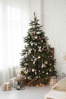 Warmes, gemütliches, schönes, modernes design des zimmers in zarten hellen farben, dekoriert mit weihnachtsbaum und kamin mit dekorativen elementen.