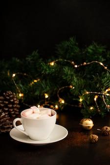 Warmes kakaogetränk mit marshmallows. weihnachts- und neujahrsgetränk. heiligabend stimmung. winterferienkonzept. dunkler hintergrund. vertikale. speicherplatz kopieren