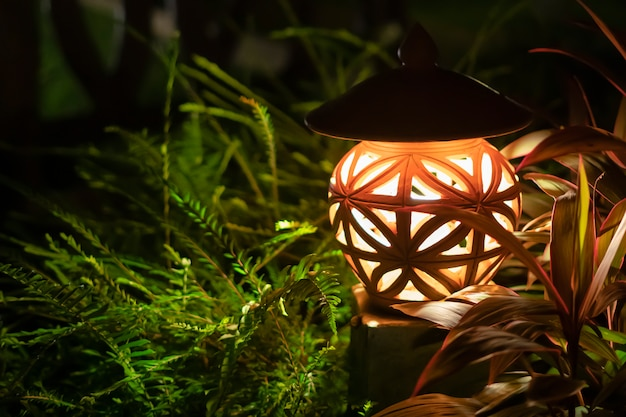 Warmes licht von einer straßenlaterne in einem grünen park. nacht, leuchtet im gras, draußen. nahansicht. design und dekoration von cottages und fazenda
