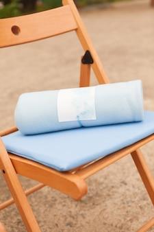 Warmes plaid auf einem braunen stuhl, eine hochzeitszeremonie im freien