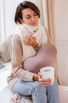 Warmes porträt der frau, die auf fensterbank mit tasse heißem teekaffee sitzt, der pullover und weißen schal trägt