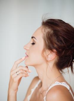 Warmes porträt des schönen jungen brunette, der ihr lippenangebot berührt