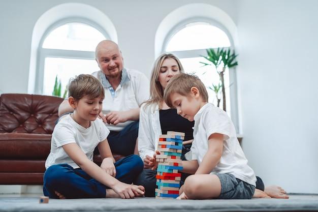 Warmes porträt einer fröhlichen familie von mutter und vater mit ihren kindern, die sie zusammen turmherausforderungsspiel spielen.