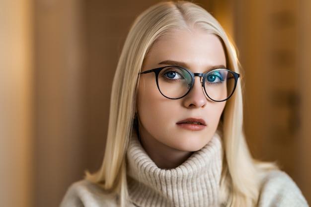 Warmes und gemütliches porträt einer blonden frau mit brille und strickpullover