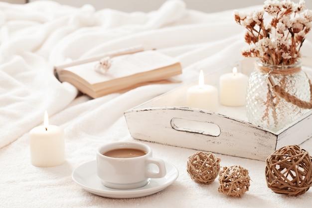 Warmes und wohnliches skandinavisches hygge konzept mit tasse kaffee, offenem buch und retro angeredetem behälter mit brennenden kerzen.