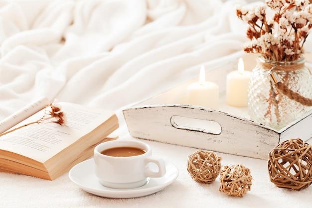 Warmes und wohnliches skandinavisches hygge-konzept. tasse kaffee, offenes buch und weißes tellersegment mit kerzen und trockenen blumen.