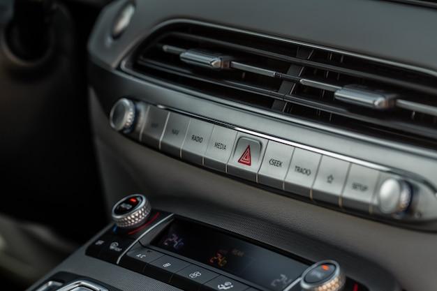 Warnblinktaste mit rotem dreieck auf dem armaturenbrett des autos. armaturenbrett für auto-medientasten. detail eines modernen autocontrollers.