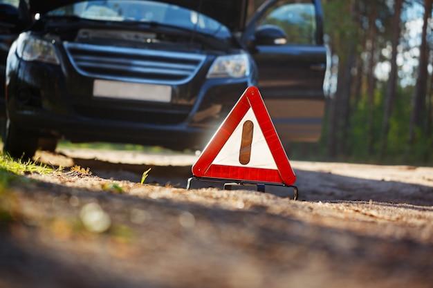 Warndreieck hinter einem kaputten auto.