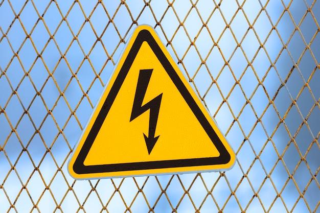 Warnschild, gelbes dreieck mit blitz auf einem zaun aus metallgitter. foto in hoher qualität