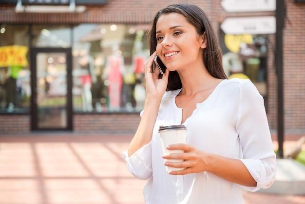 Warte auf freund. schöne junge lächelnde frau, die kaffeetasse hält und am telefon spricht, während sie im freien steht