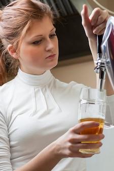 Wartefrau, die bier gießt
