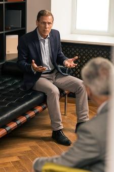 Warten auf antworten. empörter kaukasischer mann mittleren alters, der vor einem psychologen auf der couch sitzt, während er mit ihm spricht