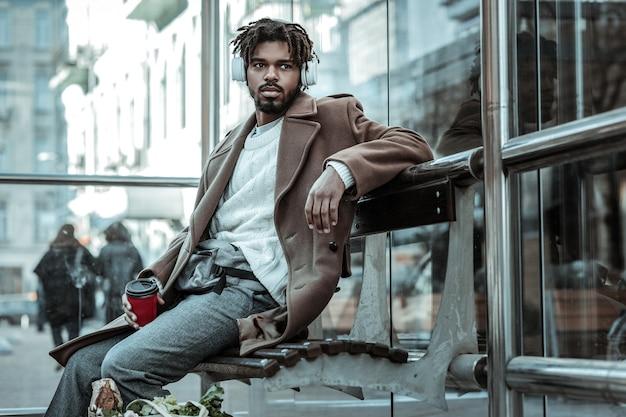 Warten auf bus. aufmerksamer mann, der auf bank sitzt, während er beiseite schaut