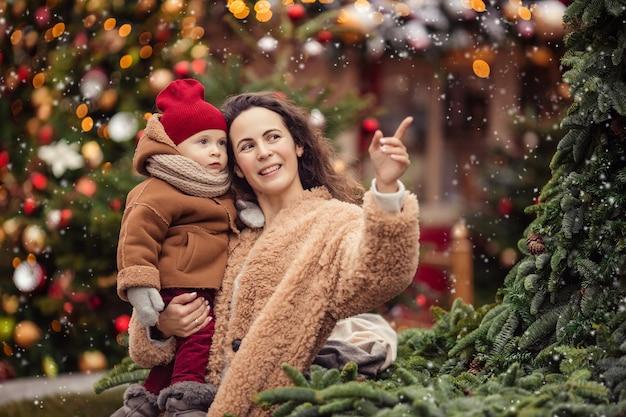 Warten auf die neujahrsferien. glückliche fröhliche mutter mit kindern auf einem spaziergang im winter auf einer geschmückten weihnachtsstraße.