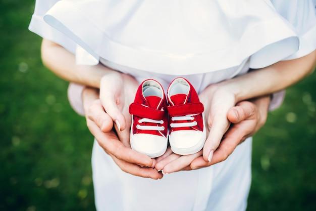 Warten auf ein wunder. kinderschuhe in elterlichen händen. schwangere frau in einem weißen sommerkleid. rote kinderschuhe.