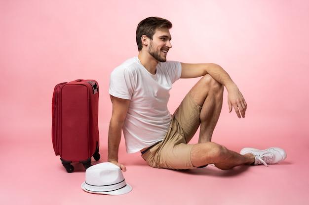 Warten auf flug. mannreisender, der auf boden mit koffer sitzt.