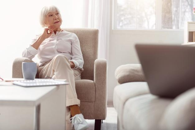Warten auf gäste. charmante ältere frau, die darauf wartet, dass jemand hereinkommt, die türen des zimmers betrachtet, während sie in ihrem sessel sitzt