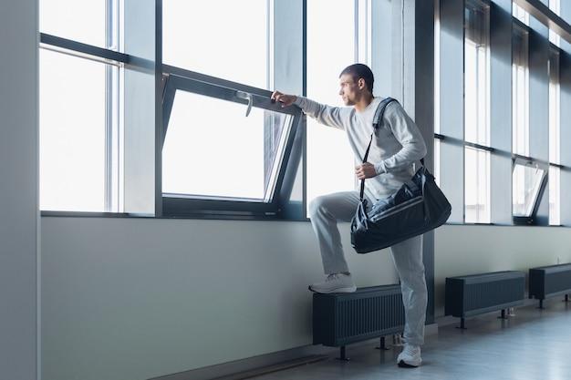 Warten auf tor. sportler, der in einem modernen verglasten gebäude, flughafen in megapolis hinuntergeht. vor dem flug zum wettkampf. professioneller, stilvoller, selbstbewusster athlet. reise, urlaub, sportlebensstil.