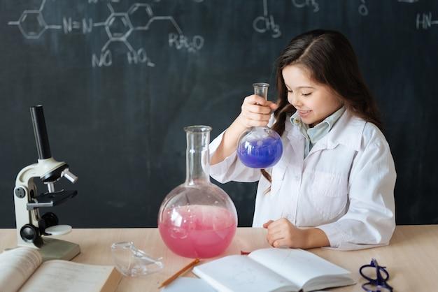 Warten auf wissenschaftliche entdeckung. crafty fähiger begeisterter schüler, der im labor sitzt und chemieunterricht genießt, während er am mikrobiologieexperiment teilnimmt