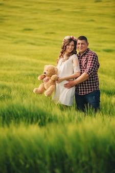 Warten baby. elternschaft. die schwangere junge frau und ihr ehemann halten gerne den teddybär in den händen und gehen auf dem feld des grünen grases ins freie.