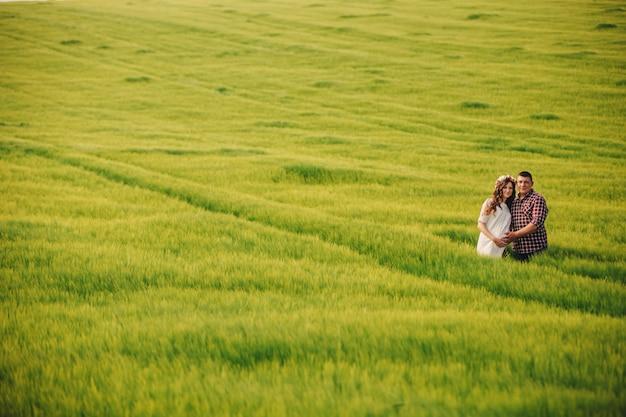 Warten baby. elternschaft. die schwangere junge frau und ihr ehemann sind glücklich, hände zu halten und im freien auf dem feld des grünen grases zu gehen. selektiver fokus.