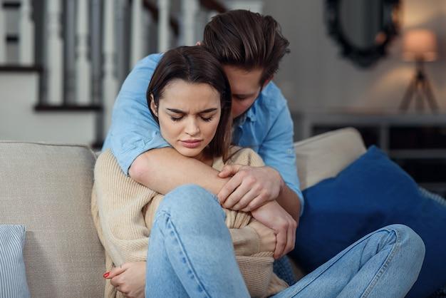 Warten. der besorgte junge mann tröstet seine freundin, während er sanft ihren arm berührt. frau hält handy und schaut freund mit beleidigung an