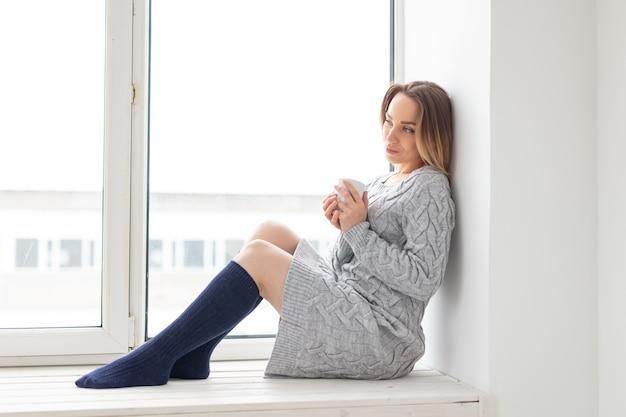 Warten, einsamkeit und schönheitskonzept - junge frau mit tasse heißem tee, der auf fensterbank sitzt