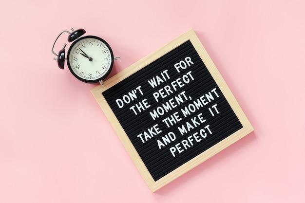 Warten sie nicht auf den perfekten moment, nehmen sie den moment und machen sie ihn perfekt. motivationszitat auf briefbrett, schwarzer wecker