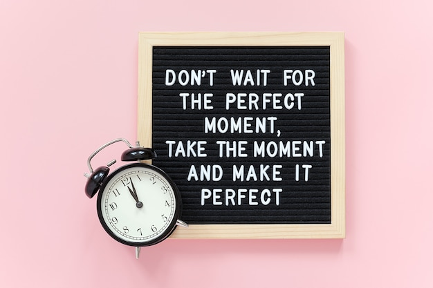 Warten sie nicht auf den perfekten moment, nehmen sie den moment und machen sie ihn perfekt. motivzitat auf briefkarton, schwarzer wecker