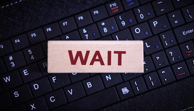 Warten sie text auf einem holzobjekt auf einer schwarzen tastatur