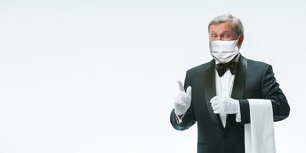 Wartet auf dich. eleganz älterer kellner in schützender gesichtsmaske auf weißem hintergrund. flyer, exemplar. café, restauranteröffnung. sicherheit während der coronavirus-pandemie. betreuung von gästen, kunden.