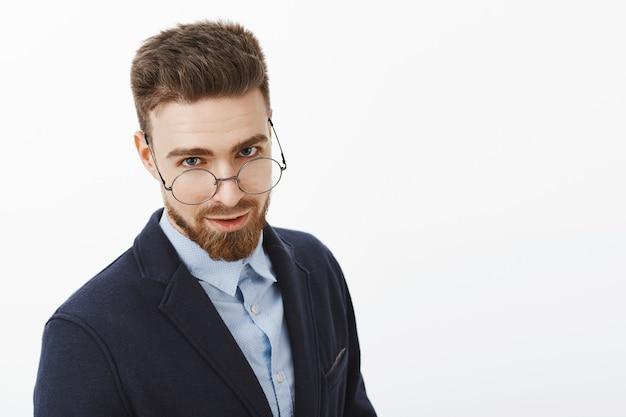 Wartezeitaufnahme des charmanten erfolgreichen und intelligenten europäischen mannes mit bart und blauen augen, die unter der brille mit dem sexy ausdruck stehen, der im eleganten anzug steht, der gegen weiße wand aufwirft