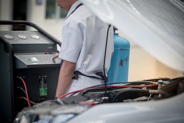 Wartung der autoklimaanlage. tankstelle. autoreparatur. automechaniker überprüfen sie den druck und das leck. zur verwendung in klimaanlagen
