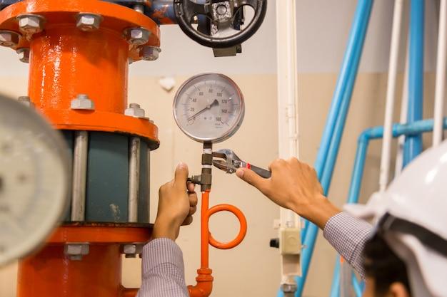 Wartung des asiatischen ingenieurs zur überprüfung der technischen daten der systemausrüstung kondensator wasserpumpe und manometer, kühlwasserpumpe mit manometer.