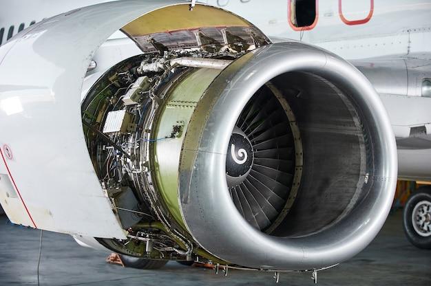 Wartung von flugzeugtriebwerken - geöffnete paneele eines großen triebwerks eines geparkten flugzeugs. niemand