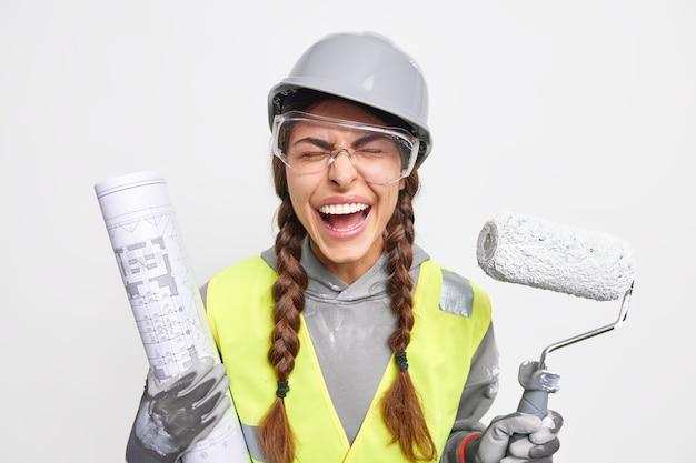 Wartungs- und besetzungskonzept. überglückliche ingenieurin posiert mit blaupause und farbroller in sicherheitskleidung, die damit beschäftigt ist, auf der baustelle isoliert über weißer wand zu rekonstruieren?