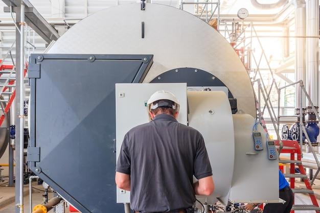 Wartungsingenieur, der mit gaskessel der heizsystemausrüstung in einem heizraum arbeitet