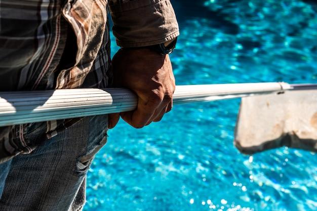 Wartungsmann, der eine poolnetzblatt-skimmerrührstange im sommer verwendet, um bereites zum baden seines pools zu verlassen.