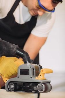 Wartungsmann, der möbel mit einer speziellen ausrüstung repariert