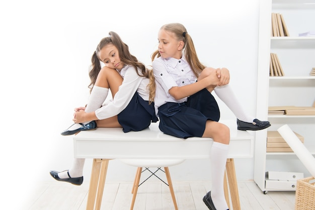 Warum bist du traurig. schulclub. kleine schulmädchen klassenkameraden freundliche kinder. schulmädchenfreunde sitzen auf dem schreibtisch. beste freunde entspannen. schulmädchen ordentliche frisur, die sich entspannt, ruhe habend. schuluniform.