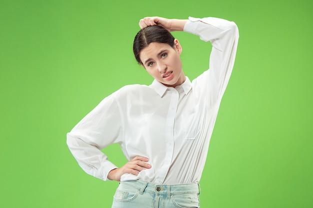 Warum das. schönes weibliches halblanges porträt lokalisiert auf trendigem grünem studiohintergrund. junge emotional überraschte, frustrierte und verwirrte frau. menschliche emotionen, gesichtsausdruckkonzept.