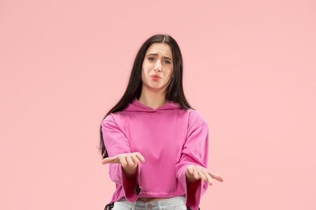 Warum das. schönes weibliches porträt der halben länge lokalisiert auf trendigem rosa studiohintergrund. junge emotional überraschte, frustrierte und verwirrte frau. menschliche emotionen, gesichtsausdruckkonzept.