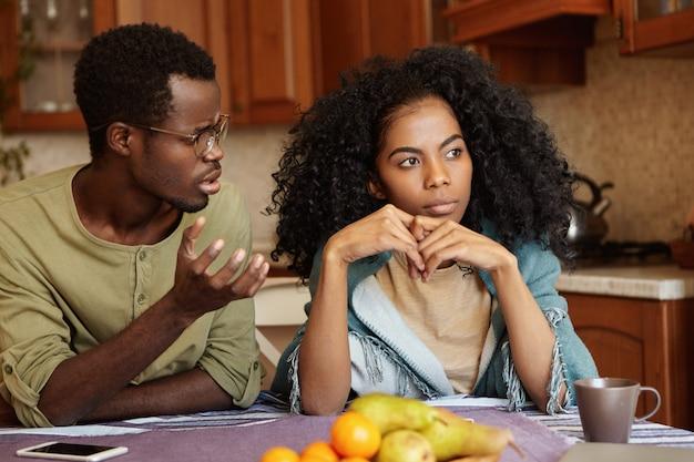Warum hast du mir das angetan? empörter depressiver junger afroamerikanischer mann in brille, der versucht, sich mit seiner gleichgültigen frau zu unterhalten, die ihn betrogen hat. beziehungsprobleme und untreue