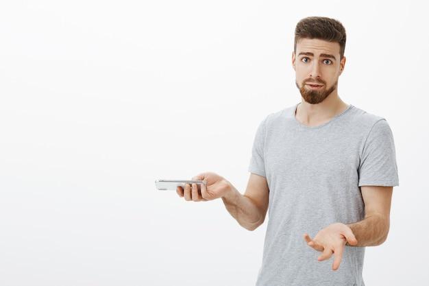 Warum mich immer wieder nerven, wenn ich telefoniere? verwirrter und belästigter dummer männlicher mann mit bart und blauen augen, der mit erhobenen handflächen zuckt und das smartphone hält, unterbrochen während eines wichtigen gesprächs