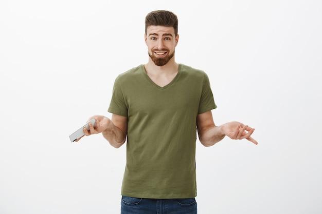 Warum nicht online bestellen? unbeschwert befragter attraktiver bärtiger mann im t-shirt, der mit den händen seitwärts zuckend das smartphone hält, ungestört, keine große sache mit dem sammeln von geschenken im internet hat