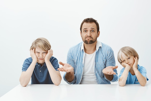Warum söhne verrückt sind. porträt des ahnungslosen nervösen schwiegervaters, der mit zwei niedlichen jungen am tisch sitzt